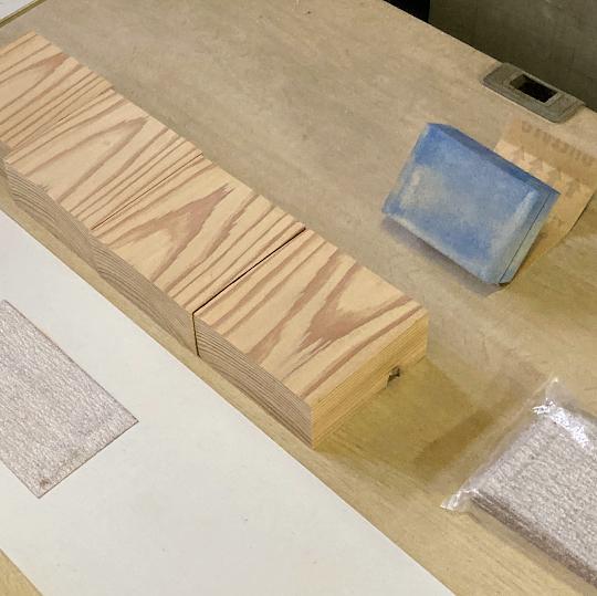 自立する杉の社名プレート製作ため表面をヤスリがけしているところ